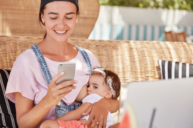 young breastfeeding mother checking Aetna insurance plan online
